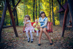 Pequeñas novias en el oscilación en parque foto de archivo libre de regalías