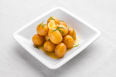 Pequeñas nuevas patatas hervidas lanzadas con las hierbas frescas en el aceite de oliva o Imágenes de archivo libres de regalías