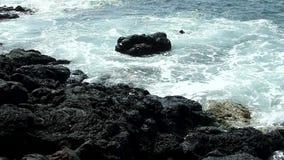 Pequeñas olas oceánicas que golpean a Lava Rock Kona Hawaii negro almacen de video