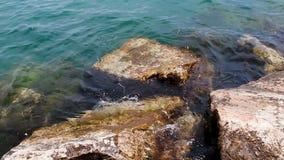 Pequeñas ondas que se lavan sobre rocas en el borde del embarcadero el lago Michigan almacen de video