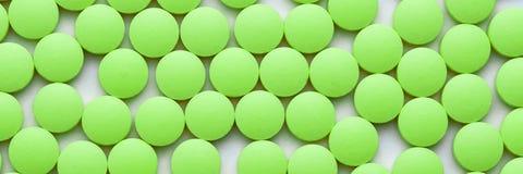 Pequeñas píldoras verdes en un primer blanco del fondo imagen de archivo libre de regalías