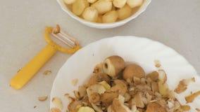Pequeñas patatas en placa, cáscara y policía en la tabla de cocina Visión superior almacen de video