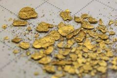 Pequeñas pepitas de oro impuras que mienten en un papel que llega a ser borroso hacia el fondo de la foto imágenes de archivo libres de regalías