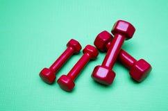 Pequeñas pesas de gimnasia en fondo verde Imagenes de archivo