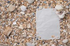Pequeñas piedras y cáscaras del mar con el documento texturizado sobre la derecha, con un espacio libre bajo texto, título, anunc Fotos de archivo