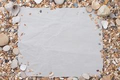 Pequeñas piedras y cáscaras del mar, en un papel texturizado, con un espacio libre bajo el texto, el título, el anuncio, el menú  Fotos de archivo libres de regalías
