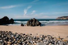 Pequeñas piedras y rocas grandes en la playa, Portugal Imágenes de archivo libres de regalías
