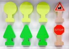 Pequeñas piezas del juguete hechas de bloques de madera con los dibujos Bajo la forma de árboles y señales de tráfico imágenes de archivo libres de regalías