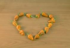 Pequeñas pimientas de chiles secadas en corazón de madera de la tabla Foto de archivo libre de regalías