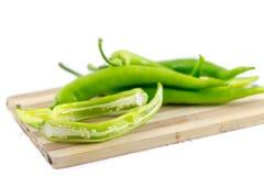 Pequeñas pimientas verdes en tabla de cortar con el fondo blanco Foto de archivo