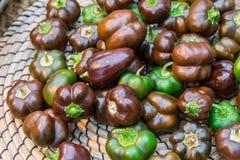 Pequeñas pimientas verdes y negras en una cesta Foto de archivo libre de regalías