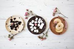 Pequeñas placas doted en la tabla de madera blanca con cosas dulces Fotos de archivo