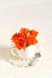 Pequeñas rosas anaranjadas en un florero blanco Foto de archivo libre de regalías