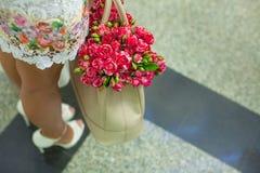 Pequeñas rosas encantadoras rojas en el bolso de las mujeres de la moda Imagen de archivo libre de regalías