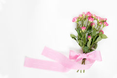 Pequeñas rosas rosadas frescas con la cinta a cuadros rosada Imágenes de archivo libres de regalías