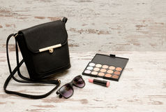 Pequeñas señoras negras bolso, gafas de sol, lápiz labial y sombreadores de ojos en fondo de madera Fotos de archivo libres de regalías