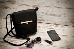 Pequeñas señoras negras bolso, gafas de sol, teléfono y lápiz labial en fondo de madera Concepto de la manera Fotografía de archivo libre de regalías