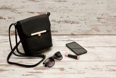 Pequeñas señoras negras bolso, gafas de sol, teléfono y lápiz labial en fondo de madera Concepto de la manera Foto de archivo libre de regalías