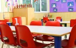 Pequeñas sillas rojas dentro de una clase de guardería Imágenes de archivo libres de regalías