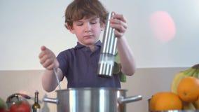 Pequeñas sonrisas divertidas del muchacho y sopa del cocinero en la cocina almacen de video