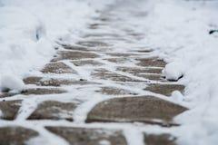 Pequeñas tejas de pavimentación nevadas, las losas después del nevadas Fondo del pavimento del invierno Uso para el trabajo de ar Imágenes de archivo libres de regalías