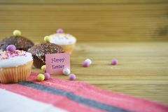 Pequeñas tortas hechas en casa con las decoraciones del huevo y palabras o texto felices de Pascua Imagen de archivo libre de regalías