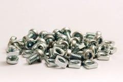 Pequeñas tuercas de acero - y - tornillos Fotos de archivo