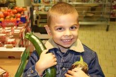 Pequeñas verduras de compra sonrientes del muchacho Fotos de archivo