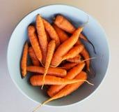 Pequeñas zanahorias de bebé en placas de sopa Imagen de archivo libre de regalías