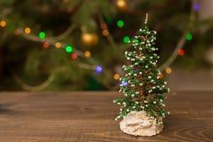 Pequeño árbol adornado de la Navidad en la tabla de madera con el fondo que brilla intensamente Fotografía de archivo libre de regalías