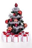 Pequeño árbol de navidad con las porciones de presentes Imagen de archivo libre de regalías