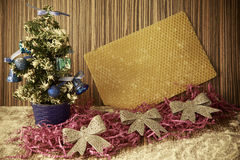 Pequeño árbol de navidad en un fondo de madera para las postales y Fotografía de archivo