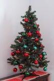 Pequeño árbol de navidad en una oficina en una esquina Imágenes de archivo libres de regalías