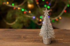 Pequeño árbol de plata adornado de la Navidad en la tabla de madera con el fondo que brilla intensamente Imágenes de archivo libres de regalías