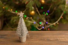 Pequeño árbol de plata adornado de la Navidad en la tabla de madera con el fondo que brilla intensamente Fotos de archivo