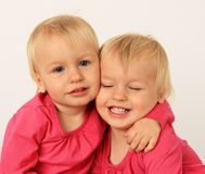 Pequeño abrazo gemelo de las muchachas imagen de archivo libre de regalías