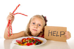 Pequeño abuso de la nutrición del niño femenino del dulce y del azúcar en la comida malsana del caramelo que pide ayuda imágenes de archivo libres de regalías