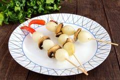 Pequeño ` adobado de la perla del ` de la cebolla en los palillos de bambú con las setas fritas Imagenes de archivo