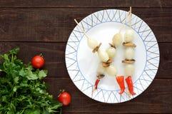 Pequeño ` adobado de la perla del ` de la cebolla en los palillos de bambú con las setas fritas en un fondo de madera oscuro Fotografía de archivo