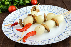 Pequeño ` adobado de la perla del ` de la cebolla en los palillos de bambú con las setas fritas en un fondo de madera oscuro Foto de archivo libre de regalías