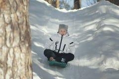 Pequeño adolescente bonito de la muchacha sledding en un bosque soleado del invierno Fotos de archivo libres de regalías