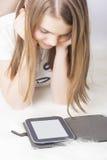 Pequeño adolescente con el eBook en casa Imagen de archivo