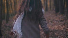 Pequeño adolescente con el pelo moreno largo y la mirada elegante Niña asustada que corre en el bosque, ella mira alrededor almacen de video