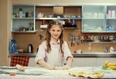 Pequeño adolescente positivo que hace la pasta en la cocina Imagen de archivo libre de regalías