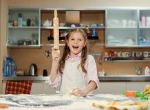 Pequeño adolescente positivo que hace la pasta en la cocina Foto de archivo libre de regalías