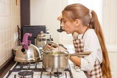 Pequeño adolescente que cocina en la cocina casera Foto de archivo libre de regalías