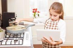 Pequeño adolescente que cocina en la cocina con el ordenador portátil Imagen de archivo libre de regalías