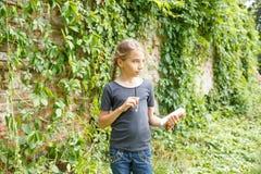 Pequeño adolescente que se coloca cerca de ruinas viejas del ladrillo Foto de archivo
