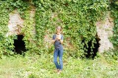 Pequeño adolescente que se coloca cerca de ruinas viejas del ladrillo Imagenes de archivo