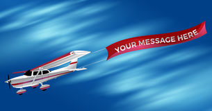 Pequeño aeroplano blanco del propulsor del solo motor que arrastra un Adverti Foto de archivo